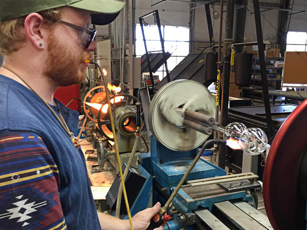 Neil Messinger, 23, a second-year student in Salem Community College's scientific glass technology program, uses a glass lathe to turn a bottle in Alloway, NJ.