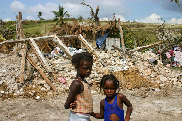Girls stand in front of their destroyed home in the Dumont section of Port Salut, Haiti. They're now living in the thatched shack that's directly behind the rubble of their home.