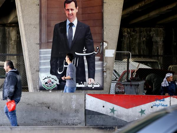 Syrian men walk past a poster bearing a portrait of President Bashar Assad in Damascus, on Feb. 27, 2016.