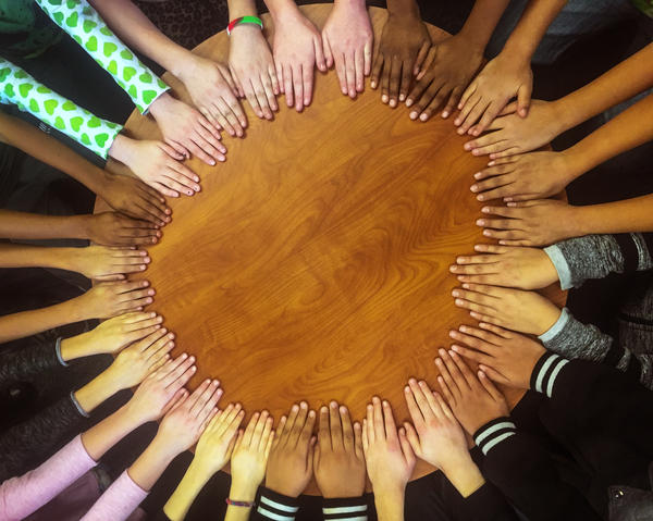 Students' hands gather in a circle in Tanya Streicher's class at Gilpin Montessori School in Denver.