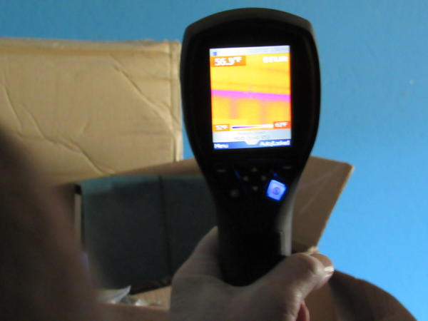 Dan Cunningham uses a thermal imaging scanner to detect gaps in wall and ceiling insulation.