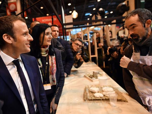 French presidential candidate Emmanuel Macron (left) speaks with a cheese maker at Paris' agriculture fair on Wednesday.