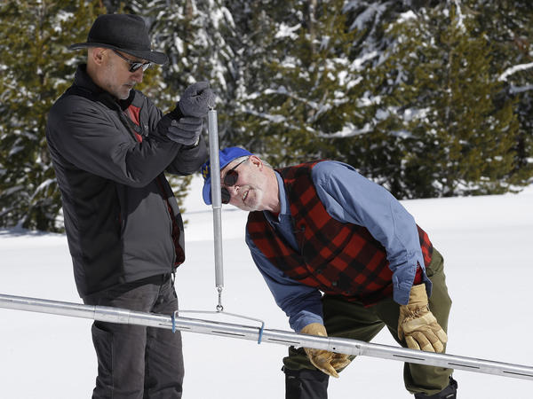 Frank Gehrke (right), California's chief snow surveyor checks the weight of the snowpack on a scale. Scientists say the snowpack is 185 percent of average, which is welcome news after the state's long drought.