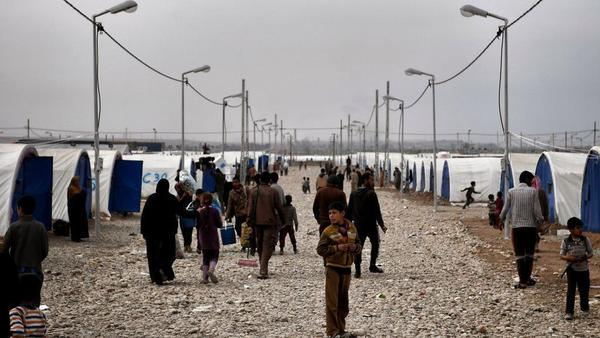 Iraqis walk at the Hamam al-Alil camp for displaced people, south of Mosul, on Wednesday, during an offensive by security forces to retake the western parts of the city from ISIS fighters.