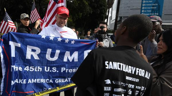 Pro-Trump supporters, left, argue with demonstrators after a Feb. 18 march in Los Angeles to protest the president's immigration policies. Sociologists say President Trump's actions and rhetoric are politically energizing both conservatives and liberals.