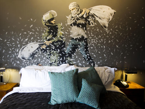 An Israeli border policeman and a Palestinian engage in a pillow fight in one of the rooms of Banksy's The Walled Off Hotel.