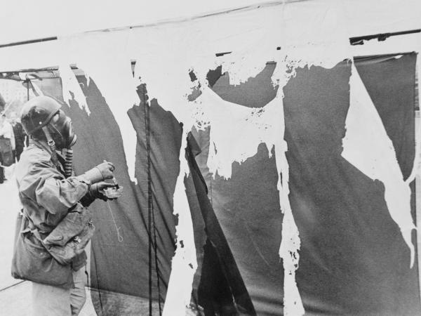 Metzger wears a gas mask while painting three nylon curtains with hydrochloric acid, causing them to disintegrate, in 1961.