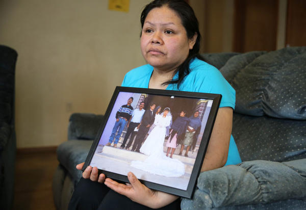 <p>Rosalina Guzman holds a photo of her and her husband, Roman, from their wedding day.</p>