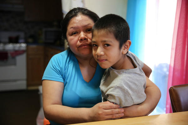 <p>Rosalina Guzman sits with her youngest son. She and her husband, Roman, have five children who were born in the United States and are citizens. </p>