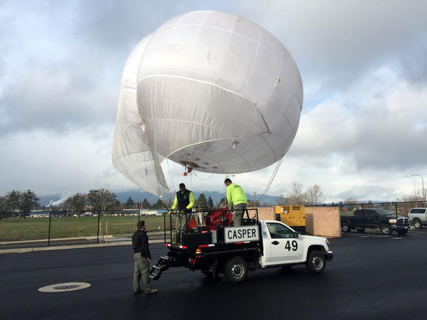 Ground crews at the Medford, Oregon airport aerially disperse crushed dry ice from this helium balloon to clear away freezing fog.