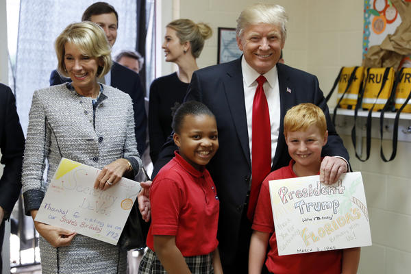 President Donald Trump and Education Secretary Betsy DeVos pose with fourth graders Janayah Chatelier, 10, left, Landon Fritz, 10, after they received cards from the children, during a tour of Saint Andrew Catholic School in Orlando, Fla.