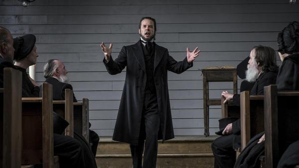 The Spite of the Hunter: Villainous preacher Guy Pearce excoriates his flock in <em>Brimstone</em>.