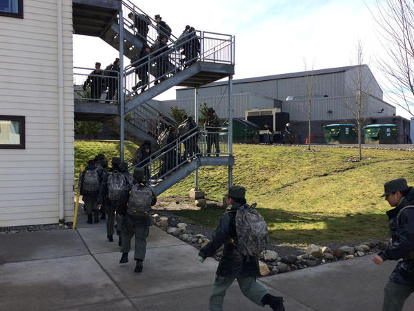 Cadets from the only female platoon, called the Eagles, run up the stairs to their bunks so they can take off their rain gear before afternoon classes begin.