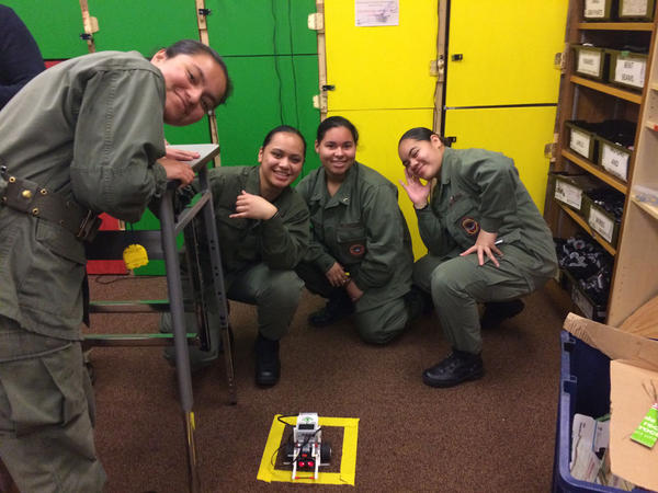 Cadets show off a robot they built and programmed in class.