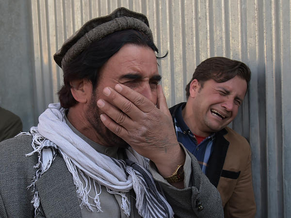 Two Afghan men weep for their relatives in front of the main gate of a Kabul military hospital Wednesday, after a deadly six-hour attack claimed by the Islamic State.