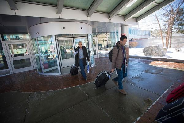 Syrian refugees Mohamad and Rashid Mahmoud leave the Manchester-Boston Regional Airport in New Hampshire in February. Their family resettled in the U.S. after a federal appeals court upheld the suspension of Trump's first ban.