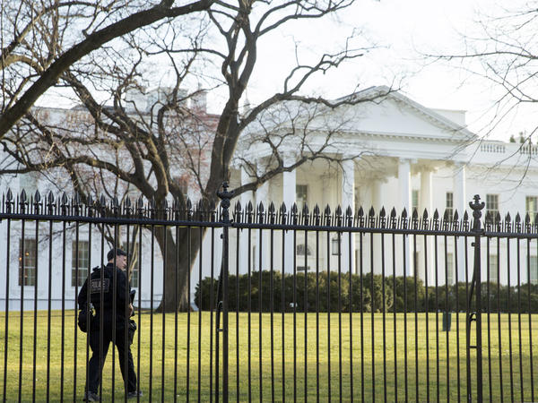 A member of the Secret Service walks the perimeter of the North Lawn of the White House in Washington last March. On Friday night, an intruder entered the White House grounds while the president was home.