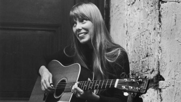 Joni Mitchell strums her guitar outside the Revolution club in London.