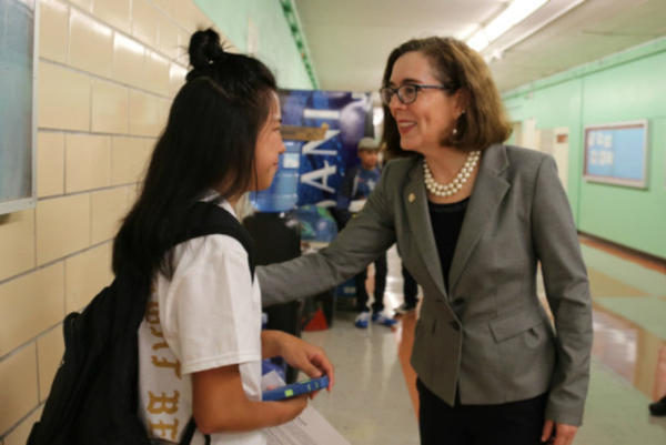 <p>Oregon Gov. Kate Brown talks with a student at Madison High School in Portland.</p>