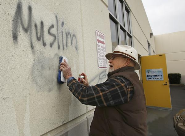 Tom Garing cleans up racist graffiti painted on the side of a mosque in what officials are calling an apparent hate crime in Roseville, Calif., in February. The Tarbiya Institute was spray-painted with a dozen obscene and racist slurs.
