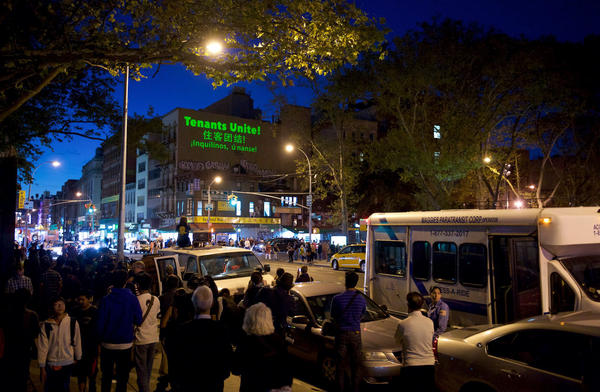"""An evening projection from the Chinatown Art Brigade, in partnership with <a href=""""http://theilluminator.org/"""" target=""""_blank"""">The Illuminator</a>, at the corner of Grand and Chrystie Streets in Chinatown, New York City, in 2016. A crowd gathered to watch the projection, including local tenants, residents and passers-by."""