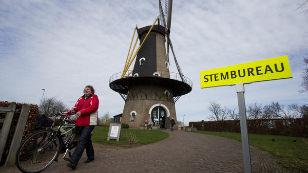 At the Kerkhovense Molen, a windmill turned polling station in Oisterwijk in south central Netherlands, a woman leaves after casting her ballot Wednesday.