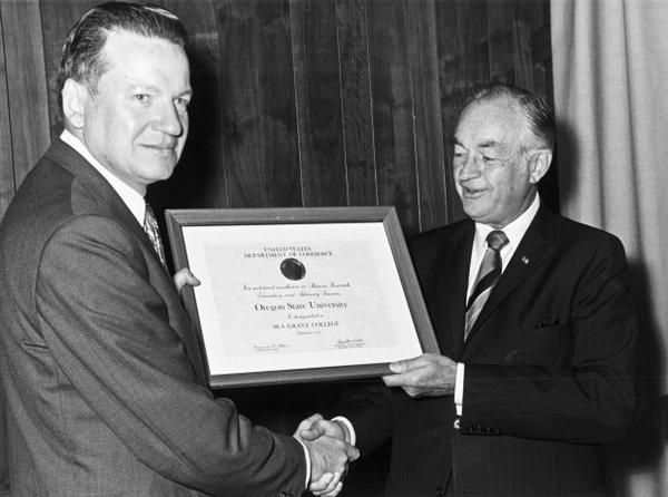 <p>U.S. Commerce Secretary Maurice Stans, right, confers official Sea Grant College designation to OSU President Rober MacVicar.</p>