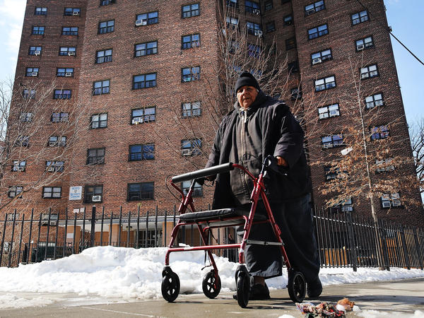 A man walks by the Farragut Houses, a public housing project in Brooklyn, N.Y. The budget blueprint President Trump released Thursday calls for the cutting of billions of dollars in funding from the Department of Housing and Urban Development.
