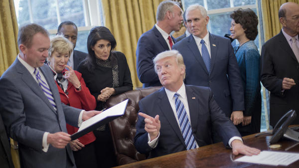 "President Donald Trump looks over towards Budget Director Mick Mulvaney, left, after signing his ""Comprehensive Plan for Reorganizing the Executive Branch"" executive order."