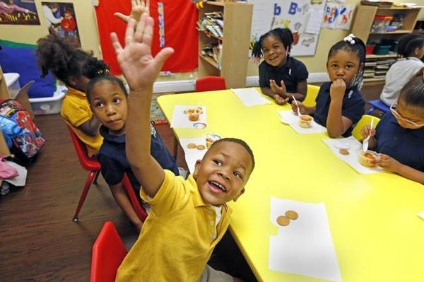 Jay'len Richardson, 5, raises his hand in class at Liberty Academy, April 19, 2016. The school is a preschool that offers high-quality care for students living in a challenged neighborhood.