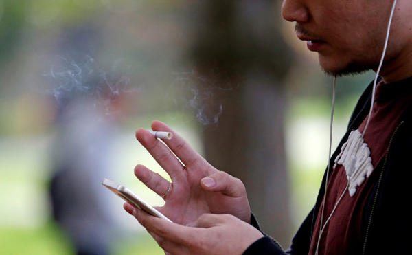 <p>A University of Washington student smokes on campus Tuesday, Oct. 27, 2015, in Seattle.</p>