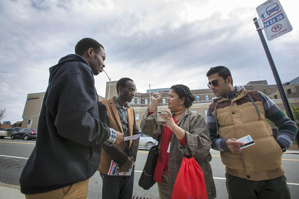 Ascentria Care Alliance, a resettlement agency based in Worcester, announced Monday that as a result of Trump's travel ban it had laid off or reduced hours for 14 employees. In this 2015 photo, an Ascentria instructor shows clients when the next WRTA bus will arrive using a smartphone app.  (Jesse Costa/WBUR)