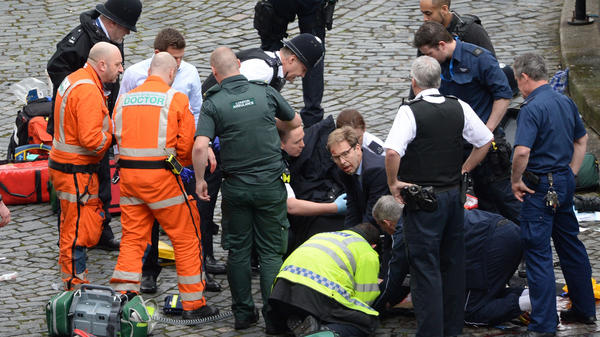 Conservative MP Tobias Ellwood helps emergency services attend to a police officer outside the Palace of Westminster, London, after a policeman was stabbed and his apparent attacker shot by officers in a major incident at the Houses of Parliament.