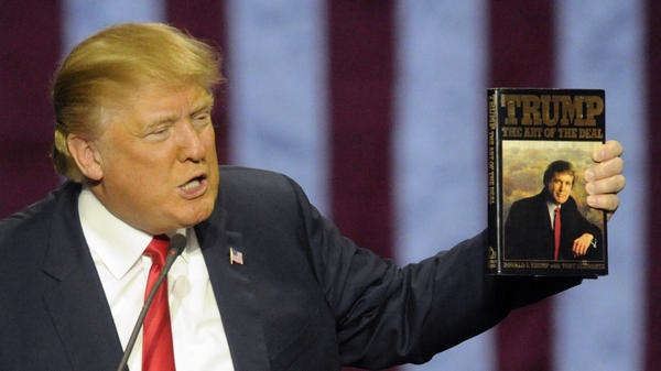 Donald Trump holds up his book <em>The Art of the Deal</em> at a campaign stop in November 2015 in Birmingham, Ala.