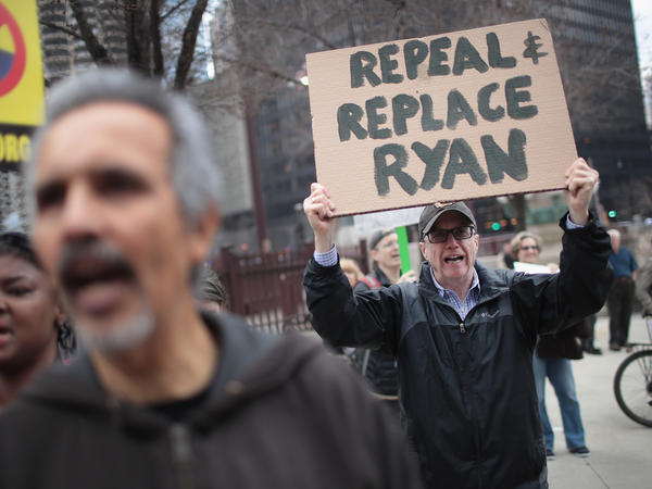 Demonstrators gather near Trump Tower after the defeat of the GOP health care plan. One man holds up a sign, urging the ouster of House Speaker Paul Ryan, who spearheaded the failed effort.