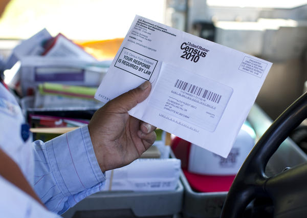 U.S. Postal Service mail carrier Thomas Russell holds a census form while working his route in 2010.