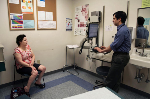 <p>In this July 11, 2014 photo, patient Amanda Thornton, left, of Aloha, Ore., speaks with primary care doctor John Guerreiro at a clinic run by the Virginia Garcia Memorial Health Center in Beaverton, Oregon. Residents of Washington County scored highest for quality of life in a new report on health care in Oregon counties.</p>