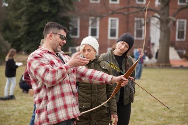 Bill Schindler often takes students out on the campus green to teach them how to use bow and arrow, as well as more primitive weapons like the atlatl. (Courtesy Washington College)