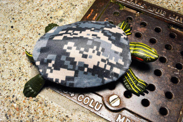 Military camouflage designed for urban combat allows reptiles to elude detection in cities as urbanization overtakes their natural habitats. In this model, a turtle wears a camouflage fabric shell covering. (Courtesy)