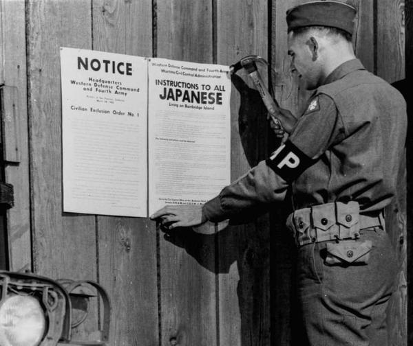 "A military police officer posting Civilian Exclusion Order No. 1, requiring ""evacuation"" of Japanese living on Bainbridge Island, Washington."