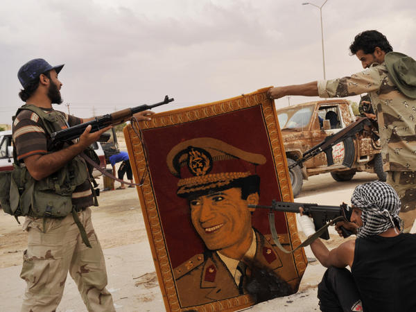 <p>Anti-Gadhafi fighters point their guns at a carpet depicting Moammar Gadhafi after taking the village of Abu Hadi, the deposed Libyan leader's birthplace, on Oct. 3. Regime loyalists who fled to the village find themselves grappling with the realities of a new nation.</p>