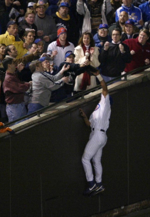 <p>As the Chicago Cubs' Moises Alou made a leaping attempt at a pop foul during the National League Championship Series, Steve Bartman (in Cubs cap and dark sweater) was among the fans reaching for the ball. While one image suggests he acted alone, the second photo tells another story.</p>