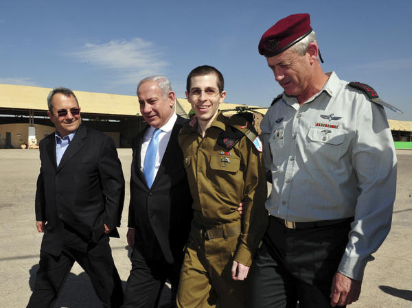 <p>Released Israeli soldier Gilad Shalit (second from right), walks with Israeli Defense Minster Ehud Barak (left), Prime Minister Benjamin Netanyahu (second from left) and Israeli Chief of Staff Lt. Gen. Benny Gantz, at the Tel Nof Air base in southern Israel on Tuesday. Shalit was freed after more than five years of captivity in the Gaza Strip.</p>