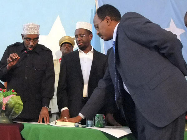 <p>Mohamed Abdullahi Mohamed, right, takes the oath of office as he is sworn in as interim prime minister of Somalia last November.</p>