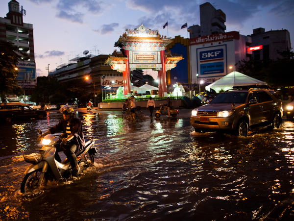 <p>Residents drive through a flooded street close to the overflowing Chao Phraya river in Bangkok on Thursday. About 400 people have died from floods in the country since late July. </p>