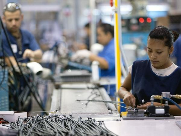 Employees of TECMA, a cross-border plant or <em>maquiladora</em>, work in Ciudad Juarez, Mexico. Business leaders say the quick delivery time of goods from Mexico to the U.S. can help revive manufacturing in North America.