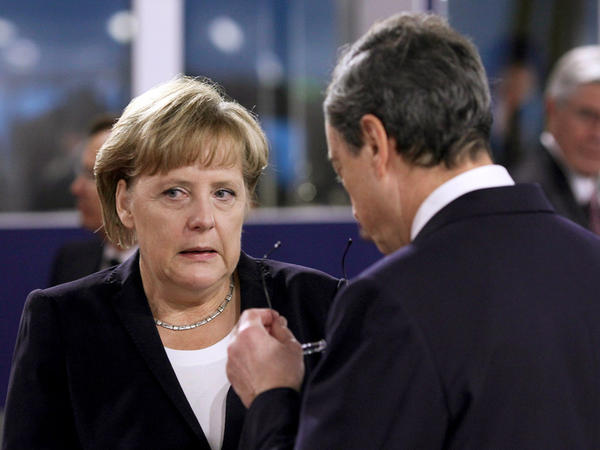 German Chancellor Angela Merkel speaks with Mario Draghi, president of the European Central Bank, on the second day of the G20 Summit in France.