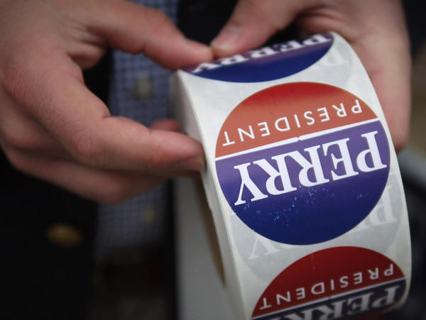 A supporter of Republican presidential candidate Texas Gov. Rick Perry passes out stickers on Dec. 16 in Cherokee, Iowa.