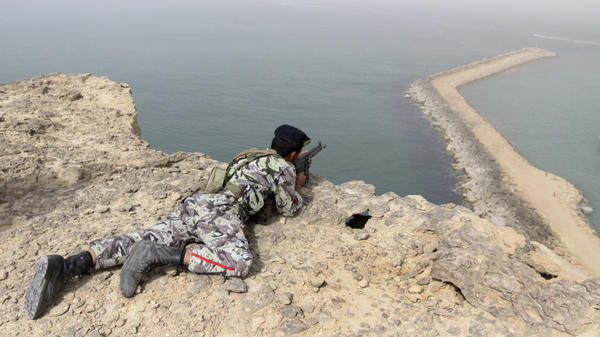 A member of the Iranian military takes position in a military exercise on the shore of the Sea of Oman in December.