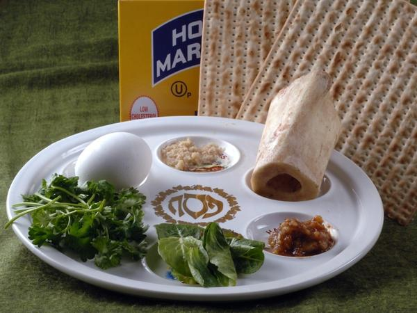 The Passover Seder plate with symbolic foods (clockwise, from top center): horseradish; a shank bone; a mixture of fruit, wine and nuts called <em>haroset;</em> lettuce, parsley and an egg.